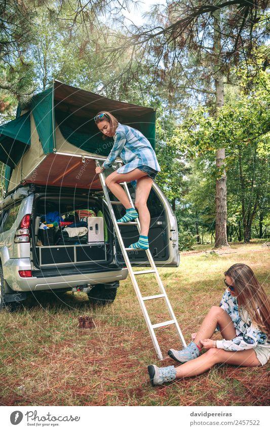 Frau, die die Leiter vom Zelt über das Auto steigt. Lifestyle Freude Glück Erholung Freizeit & Hobby Ferien & Urlaub & Reisen Ausflug Abenteuer Camping Sommer