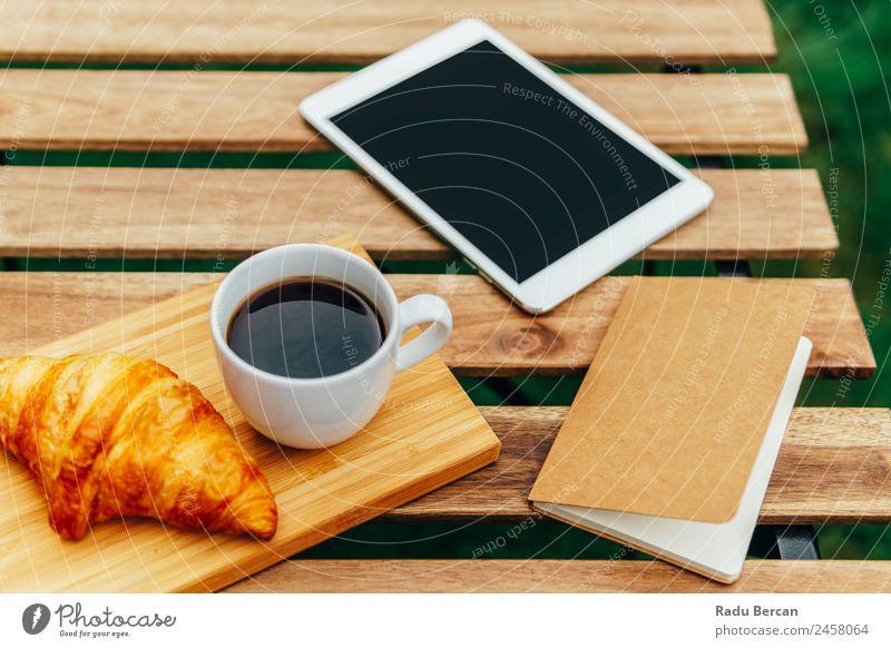 Frühstück am Morgen im Grünen Garten mit französischem Croissant, Kaffeetasse, Orangensaft, Tablette und Notizbuch auf Holztisch Tisch Hintergrundbild Sommer