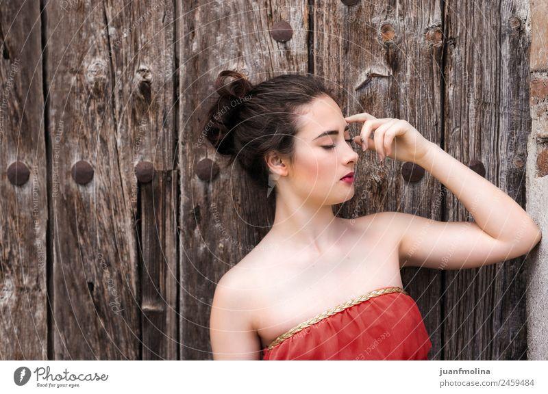Porträt eines Mädchens in rotem Kleid an einer Holztür Lifestyle elegant Stil schön Sommer Mensch feminin Frau Erwachsene 18-30 Jahre Jugendliche Tür Gefühle