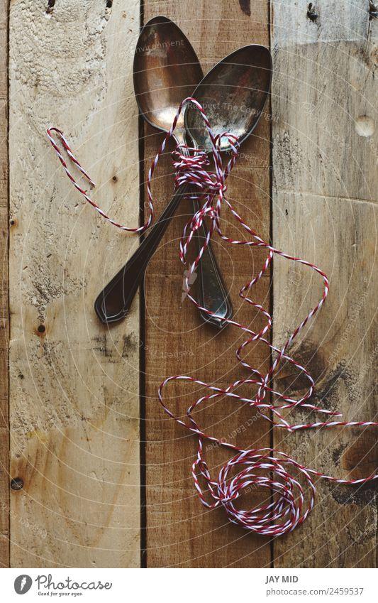 Vintage-Metalllöffel, auf Holzuntergrund Löffel Design Tisch Restaurant Werkzeug Seil Sammlung Schnur alt glänzend lustig retro braun weiß Kreativität Tradition