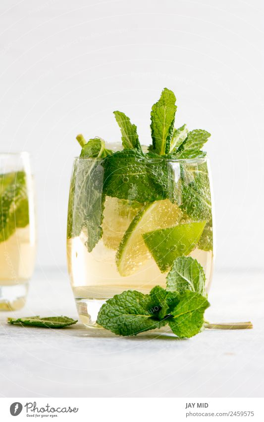 Mojito-Cocktail mit Rum, Limette und Soda Frucht Kräuter & Gewürze Getränk Erfrischungsgetränk Limonade Saft Alkohol Longdrink Glas exotisch Sommer Tisch Blatt