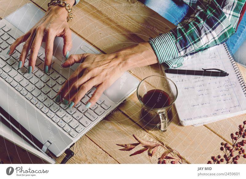 Frau schreibt am Computer, trägt kariertes Hemd und lässige St. Kaffee Lifestyle Freude Freizeit & Hobby Schreibtisch Tisch Bildung Erwachsenenbildung lernen