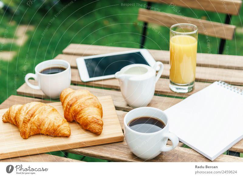 Frühstück am Morgen im Grünen Garten mit französischem Croissant, Kaffeetasse, Orangensaft, Tablette und Notizbuch auf Holztisch Tisch Hintergrundbild weiß