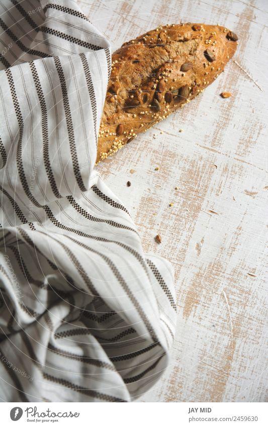 rustikales Brot, umhüllt von gestreiftem Stoff Lebensmittel Frühstück Bioprodukte Diät Menschengruppe frisch braun weiß Tradition Brote Brotlaib Mais Samenbrot