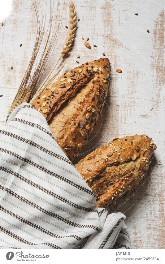 rustikales Saatgutbrot, umhüllt von gestreiftem Stoff Lebensmittel Brot Frühstück Bioprodukte Diät Menschengruppe frisch braun weiß Tradition Brote Brotlaib
