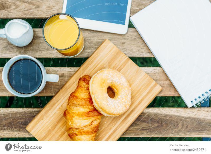 Frühstück im Grünen Garten mit französischem Croissant, Donuts, Kaffeetasse, Orangensaft, Tablette und Notizen Buch auf Holztisch Tisch Hintergrundbild Morgen