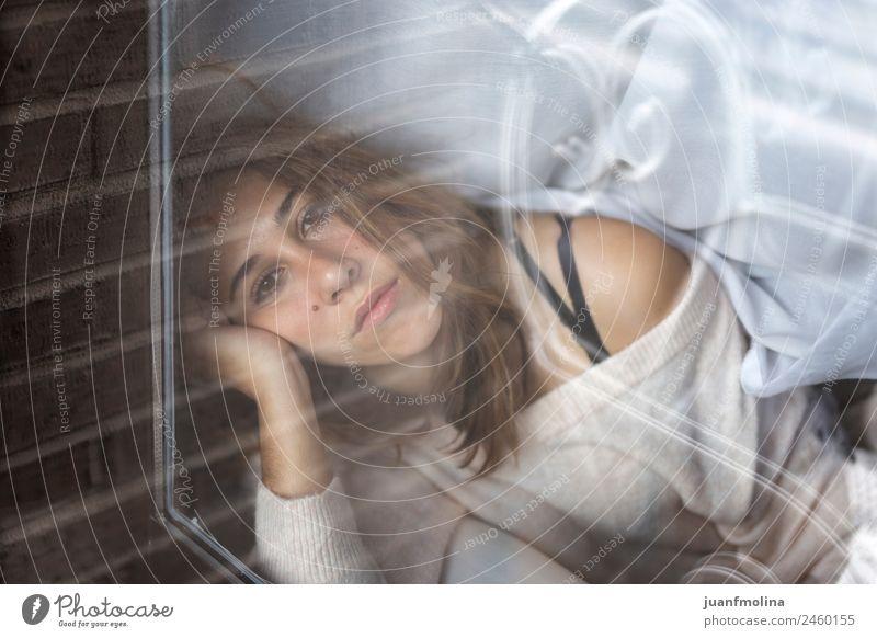 Frau zu Hause, die durch das Glas schaut. Lifestyle schön Dachboden Mensch Erwachsene Gesicht Fenster Pullover sitzen Traurigkeit natürlich jung heimwärts