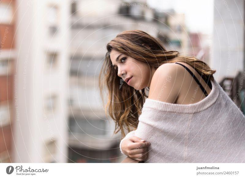 Frau schaut von ihrem Balkon auf die Stadt. Lifestyle schön Gesicht Wohnung Mensch Erwachsene Leben Straße Pullover Denken träumen elegant Gefühle Einsamkeit