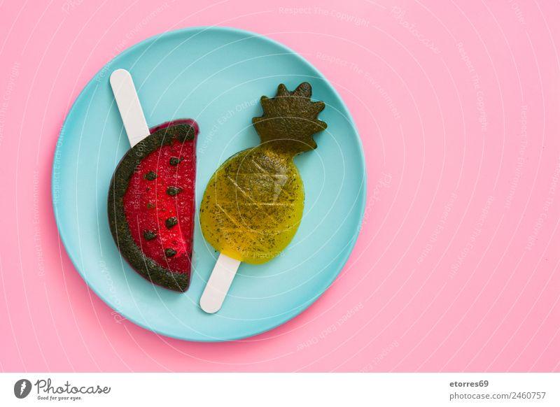 Ananas- und Wassermelonenstiele auf rosa Hintergrund. Lebensmittel Frucht Dessert Speiseeis Süßwaren Ernährung Sommer Sommerurlaub blau gelb grün rot Eis Snack