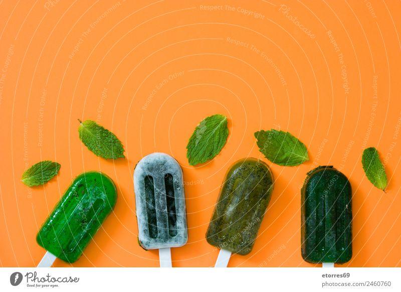 Grüne gefrorene Eis am Stiel auf orangem Hintergrund. Draufsicht. Kopierbereich Lebensmittel Frucht Speiseeis Sommer Sommerurlaub exotisch kalt Tiefkühlkost