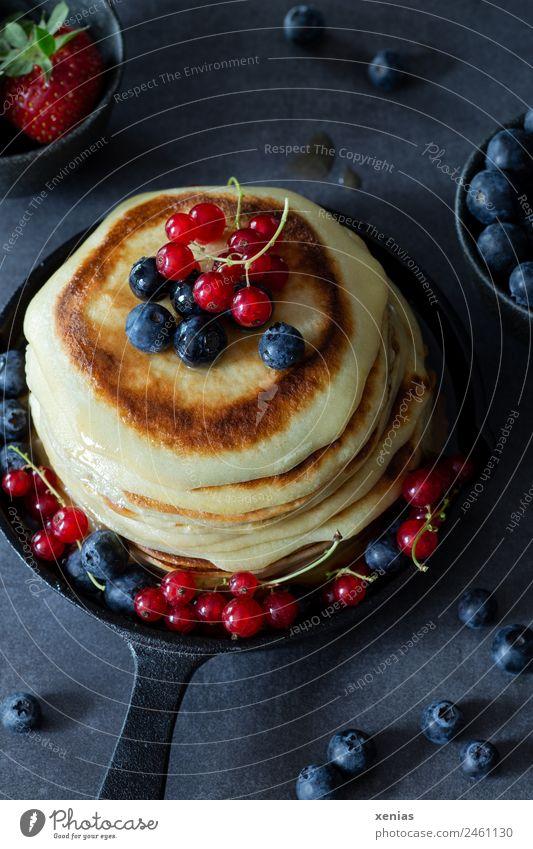 Kleine Pfannkuchen mit Blaubeeren und roten Johannisbeeren in gusseiserner Pfanne Frucht Teigwaren Backwaren Erdbeeren Zuckersirup Frühstück Büffet Brunch