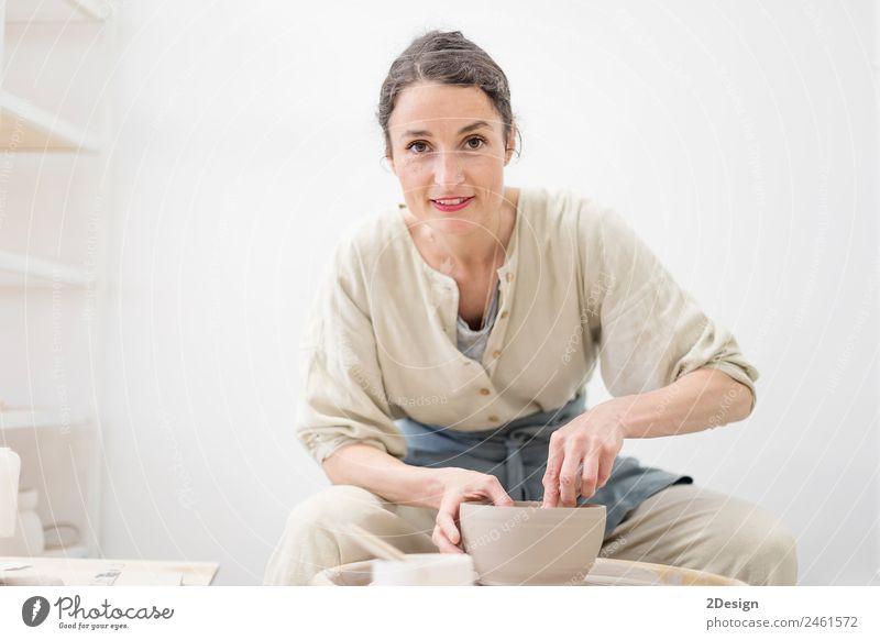 Junge Frau sitzt am Tisch und stellt Ton- oder Keramikbecher her. Geschirr Lifestyle Freizeit & Hobby Handarbeit Arbeit & Erwerbstätigkeit Beruf Handwerker