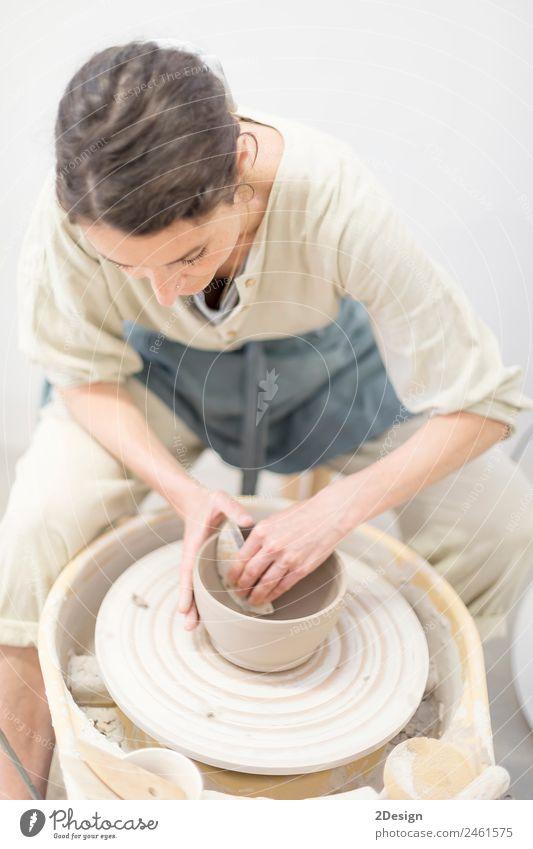 Junge Frau sitzt am Tisch und stellt Ton- oder Keramikbecher her. Geschirr Freizeit & Hobby Handarbeit Arbeit & Erwerbstätigkeit Beruf Handwerker Arbeitsplatz
