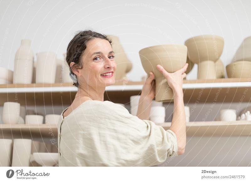 Schöner Keramikerbesitzer, der auf die Kamera schaut, während er lächelt. Topf Freizeit & Hobby Handarbeit Arbeit & Erwerbstätigkeit Beruf Handwerker