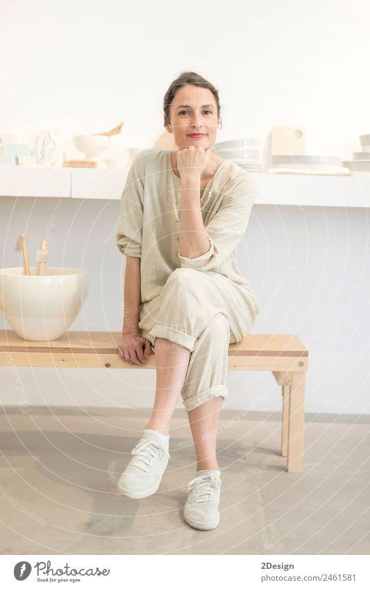 Frau in Arbeitskleidung in ihrer Werkstatt am Tisch mit handgefertigten Gegenständen Geschirr Lifestyle Freizeit & Hobby Handarbeit Arbeit & Erwerbstätigkeit