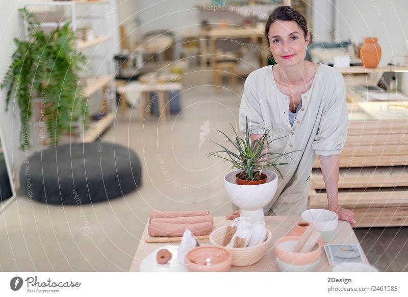 Frau in Arbeitskleidung in ihrer Werkstatt am Tisch mit handgefertigten Gegenständen Geschirr Lifestyle elegant Freizeit & Hobby Handarbeit