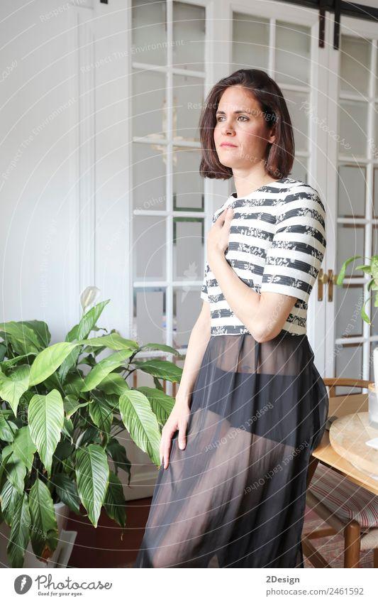 junge schöne Dame, die im Wohnzimmer neben einem Fenster posiert. Lifestyle Reichtum elegant Stil Glück Körper Erholung Möbel Mensch feminin Junge Frau