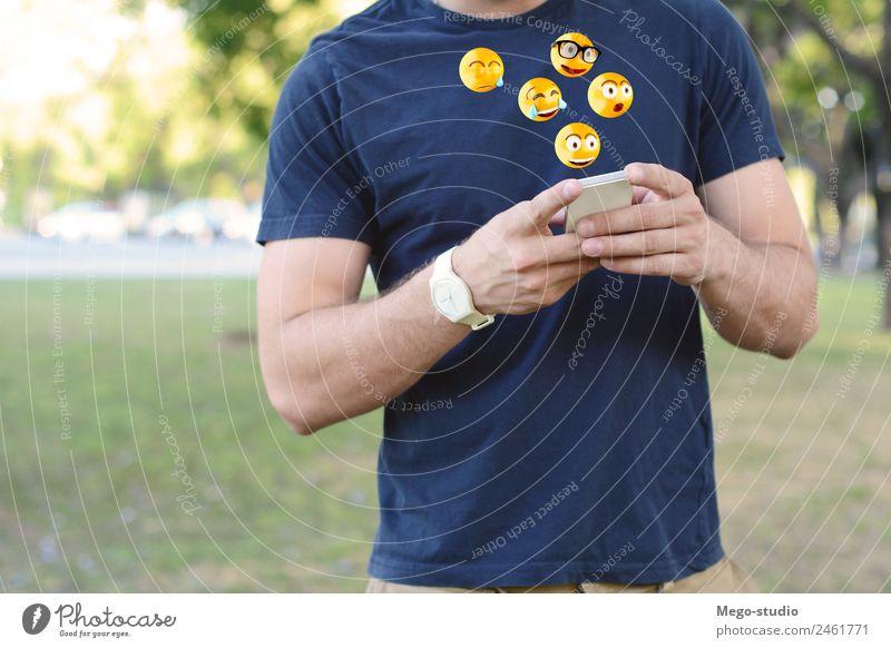 junger lateinamerikanischer Mann, der auf seinem Handy mit Emoji-Emoticons schreibt. Lifestyle Stil Glück Telefon PDA Technik & Technologie Mensch Erwachsene