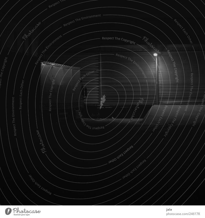 one night in trostlosistan Haus Industrieanlage Bauwerk Gebäude Fassade Rolltor Laterne Lastwagen dunkel trist schwarz weiß Schwarzweißfoto Außenaufnahme