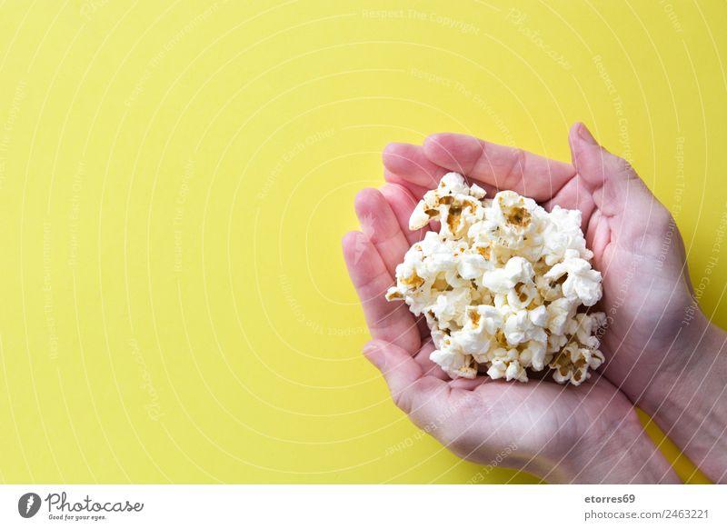 Frau mit Popcorn in der Hand auf gelbem Hintergrund. Kopierbereich Lebensmittel Ernährung Essen Bioprodukte Vegetarische Ernährung Diät Fastfood Fingerfood