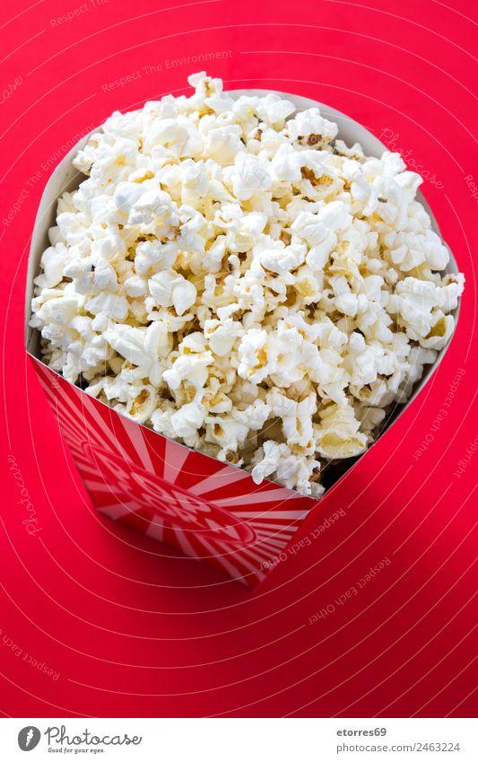 Gestreifte Box mit Popcorn auf rotem Hintergrund. Lebensmittel Ernährung Essen Bioprodukte Fingerfood Popkorn Kino Salz Butter Snack weiß lecker Mais Streifen
