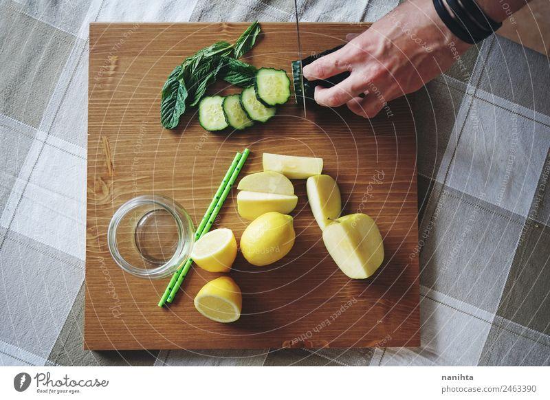 Mann, der frisches Gemüse und Obst schneidet. Lebensmittel Frucht Apfel Kräuter & Gewürze Gurke Minzeblatt Zitrone Gurkenscheibe Ernährung Frühstück Bioprodukte