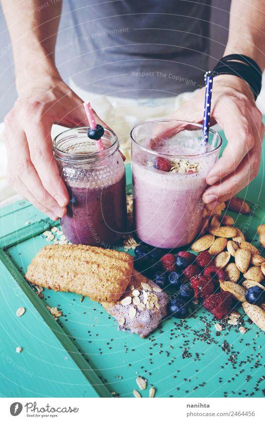 Mann, der zwei Beeren-Smoothies hält. Lebensmittel Frucht Getreide Teigwaren Backwaren Mandel Chia Plätzchen Hafer Milchshake Ernährung Essen Frühstück