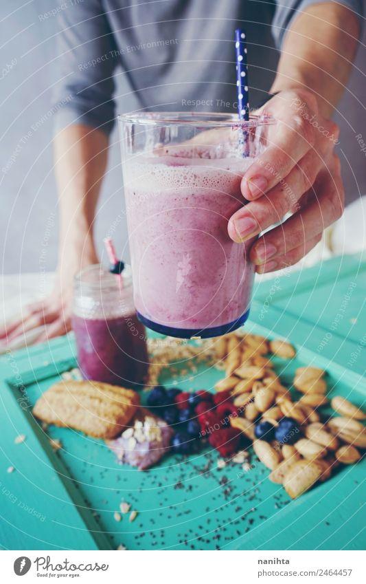 Mann hält einen Milchshake aus Beeren und Haferflocken. Frucht Dessert Mandel Plätzchen Frühstück Bioprodukte Vegetarische Ernährung Getränk trinken