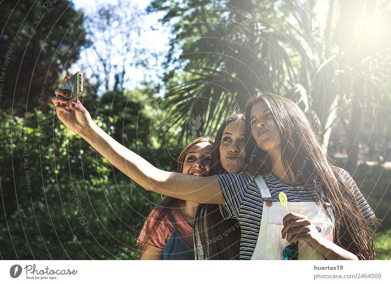 Drei schöne junge Frauen Lifestyle Stil Freude Mensch feminin Junge Frau Jugendliche Freundschaft Gesicht 3 Schönes Wetter Baum Park Mode Hut lachen grün