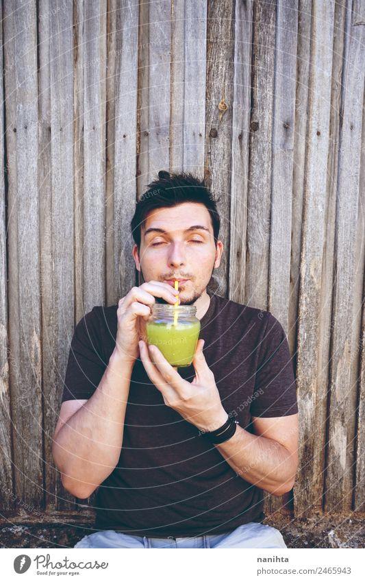Junger Mann trinkt Gemüsesaft Bioprodukte Vegetarische Ernährung Getränk trinken Erfrischungsgetränk Saft Milchshake Glas Trinkhalm Lifestyle Stil