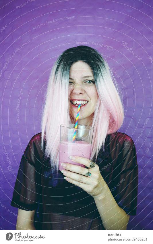 Junge glückliche Frau, die einen Milchshake trinkt. Frucht Ernährung Getränk trinken Erfrischungsgetränk Saft Lifestyle Stil Freude Haare & Frisuren