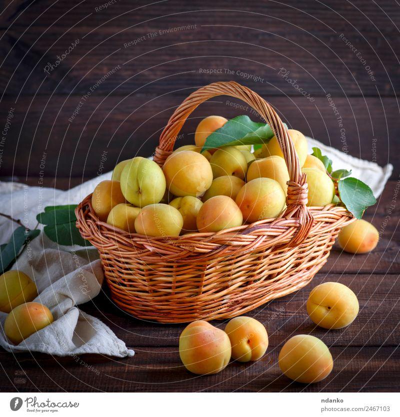 Aprikosen in einem braunen Weidenkorb Frucht Ernährung Vegetarische Ernährung Diät Tisch Natur Blatt Holz frisch lecker natürlich saftig gelb Farbe Korb