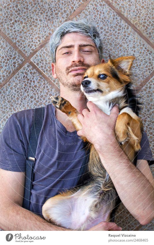 Porträt eines Mannes mit seinem Hund auf dem Boden liegend. Tier Haustier Backstein berühren genießen Liebe Zusammensein modern natürlich positiv blau braun