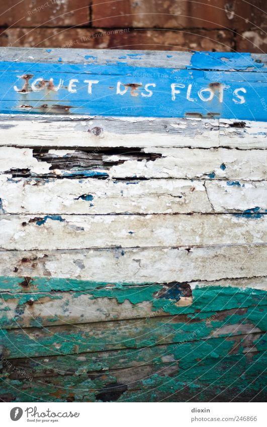 Spielball der Wellen alt Wasserfahrzeug kaputt Schriftzeichen Vergänglichkeit Schifffahrt Lack abblättern Fischerboot Schiffswrack Schiffsrumpf Bootslack