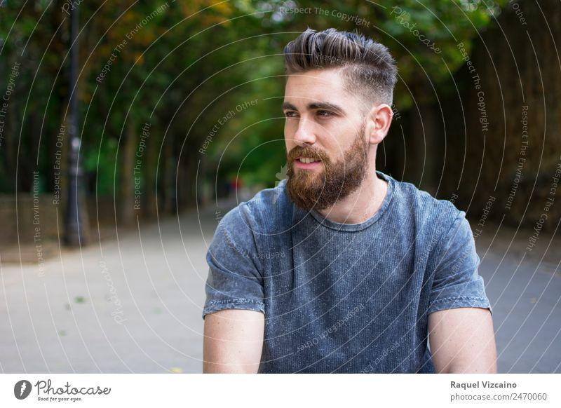 Mann sitzt im Frühling im Freien. Mensch maskulin Junger Mann Jugendliche Kopf Gesicht Gesäß 1 18-30 Jahre Erwachsene Park T-Shirt blond Vollbart fangen Lächeln