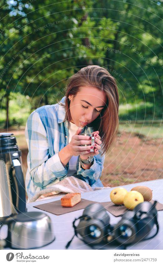 Frau mit einer Tasse heißem Kaffee, die unter der Decke sitzt. Frucht Frühstück Lifestyle Erholung Freizeit & Hobby Ferien & Urlaub & Reisen Ausflug Abenteuer