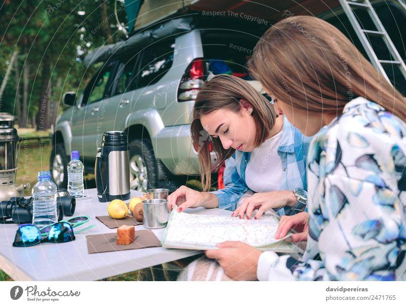 Junge Frauen, die eine Roadmap mit 4x4 im Hintergrund suchen. Frühstück Kaffee Lifestyle Freude Erholung Freizeit & Hobby Ferien & Urlaub & Reisen Ausflug