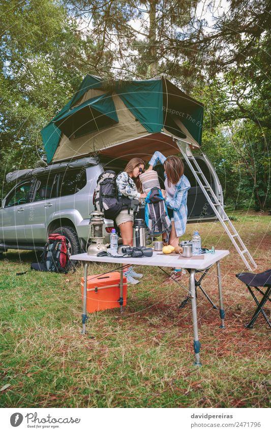 Junge Frauen auf dem Campingplatz, die eine Decke im Rucksack packen. Lifestyle Freude Glück Erholung Freizeit & Hobby Ferien & Urlaub & Reisen Ausflug