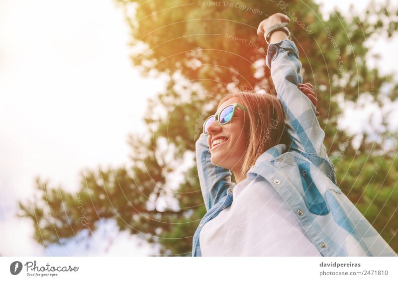 Frau mit Sonnenbrille, die ihre Arme über den Naturhintergrund hebt. Lifestyle Freude Glück Erholung Freizeit & Hobby Freiheit Sommer Erfolg Mensch Erwachsene