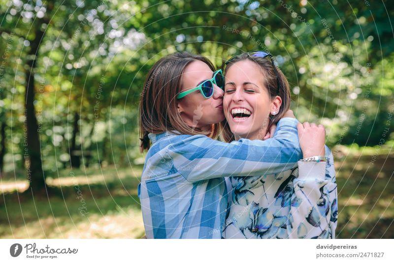 Frau küssend und umarmend zur Freundin lachtend Lifestyle Freude Glück schön Freizeit & Hobby Sommer Mensch Erwachsene Freundschaft Paar Jugendliche Natur