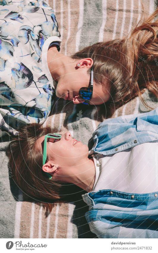 Freundinnen mit Sonnenbrille sehen sich liegend an. Lifestyle Freude Glück schön Erholung Freizeit & Hobby Sommer Sonnenbad Mensch Frau Erwachsene Freundschaft
