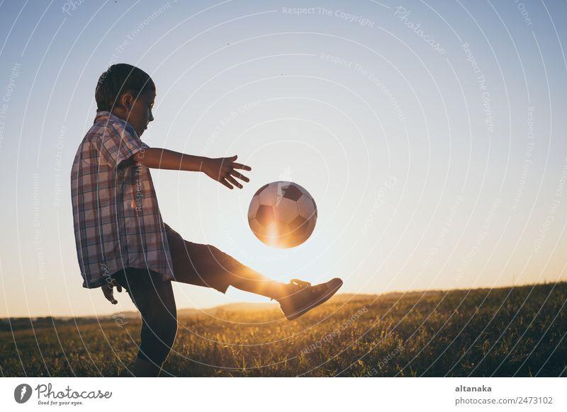 Kleiner Junge spielt auf dem Feld mit einem Fussball. Begriff des Sports. Lifestyle Freude Glück Erholung Freizeit & Hobby Spielen Sommer Fußball Kind Mensch