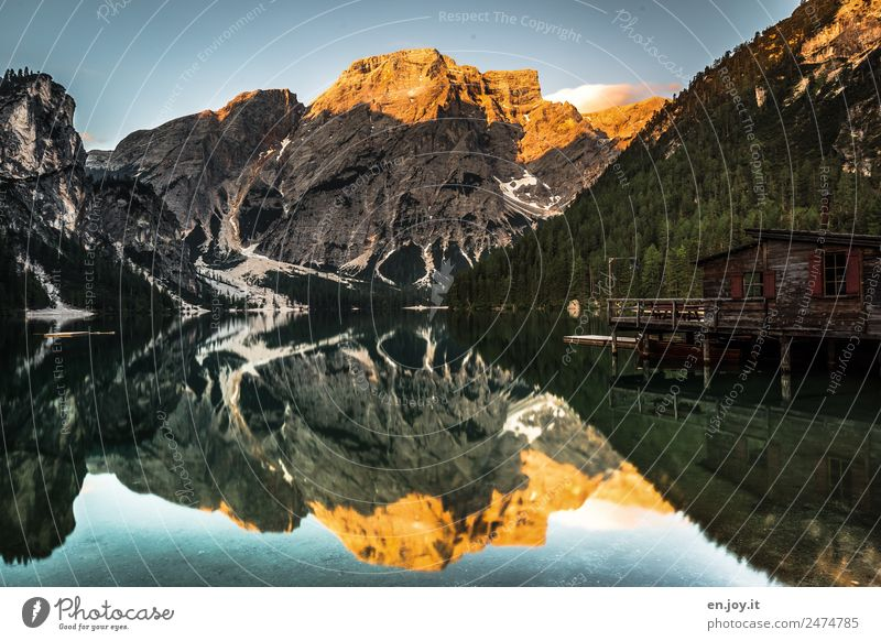 Der Pragser Wildsee mit Spiegelung der Berge, des Bootshauses mit Alpenglühen Ferien & Urlaub & Reisen Tourismus Ausflug Sommer Sommerurlaub Berge u. Gebirge