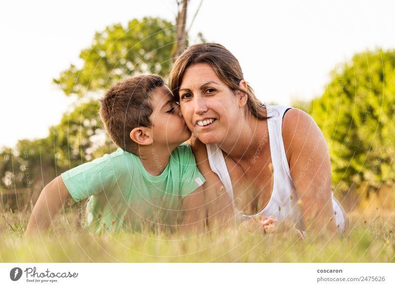 Kleiner Junge, der seine Mutter im Sommer auf einem Feld küsst. Lifestyle Freude Glück schön Sonne Kindererziehung Baby Kleinkind Frau Erwachsene Eltern