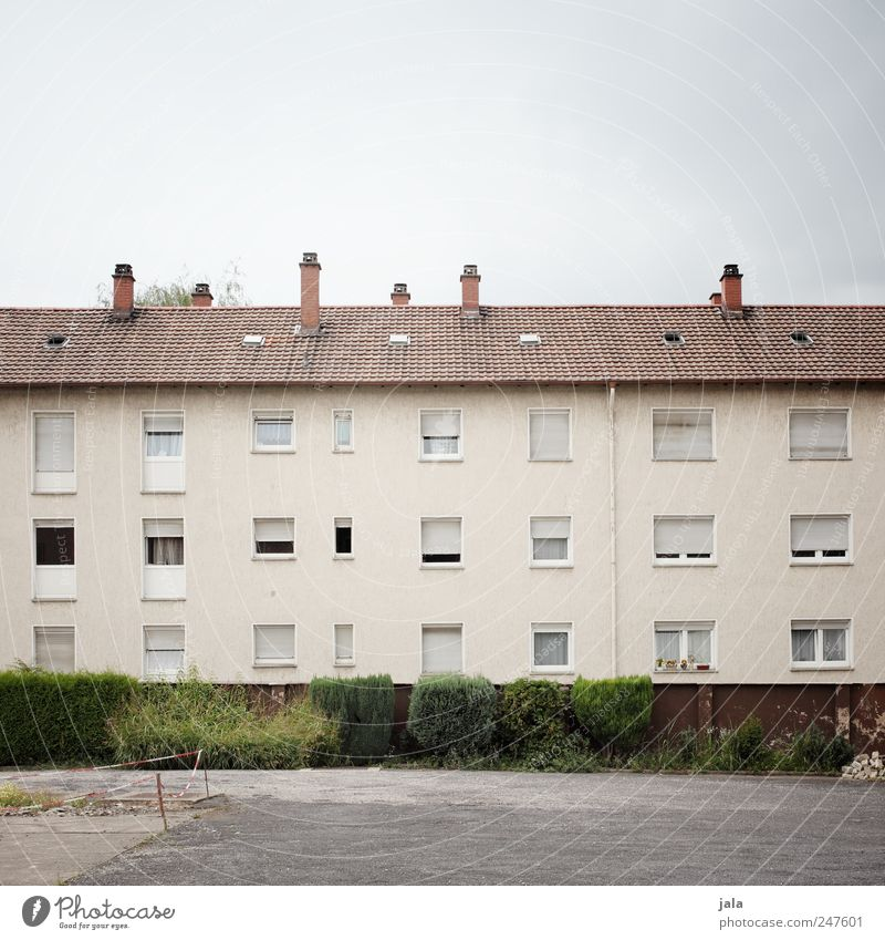 wohnblock Himmel Sträucher Haus Platz Bauwerk Gebäude Mauer Wand Fassade Fenster Tür Schornstein trist Farbfoto Außenaufnahme Menschenleer Textfreiraum oben Tag