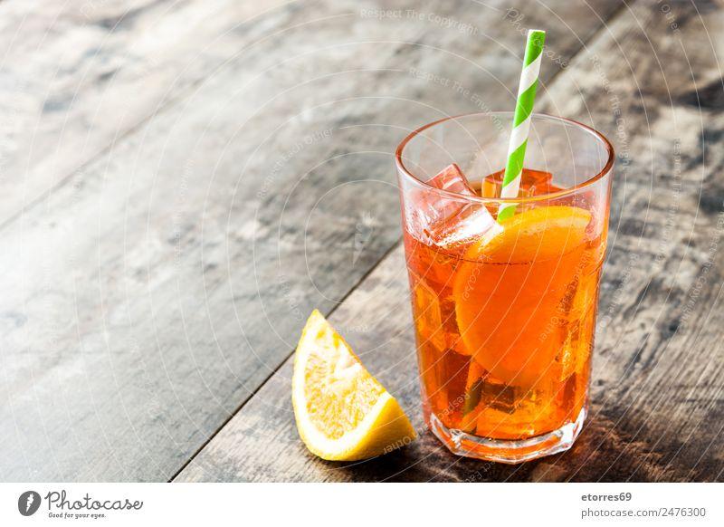 Aperol Schorle Cocktail Getränk Erfrischungsgetränk Alkohol Spirituosen Longdrink Glas Sommer Sommerurlaub gut kalt süß orange Holztisch Eis Farbfoto