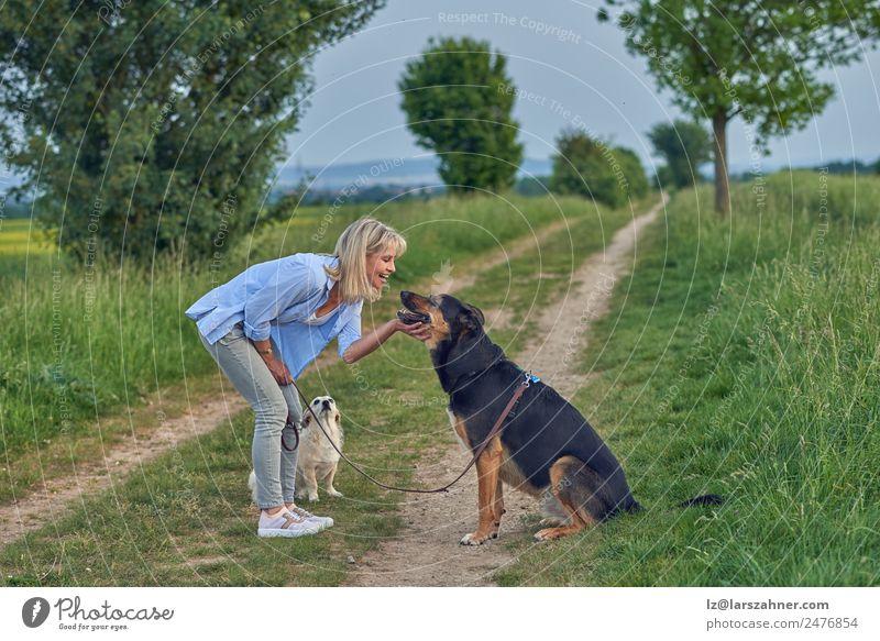 Lächelnde Frau, die ihren Hund auf der Landstraße streichelt. Sommer Erwachsene Freundschaft Landschaft Tier Wege & Pfade blond lachen Lehre ländlich