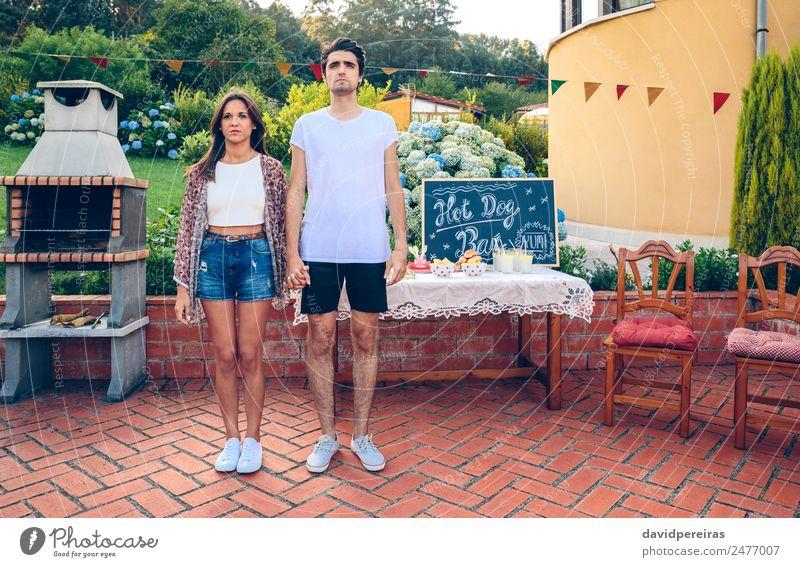 Paar steht in einem Sommergrill im Freien. Brot Brötchen Mittagessen Fastfood Getränk Limonade Lifestyle Freude Erholung Garten Tisch Tafel Mensch Frau