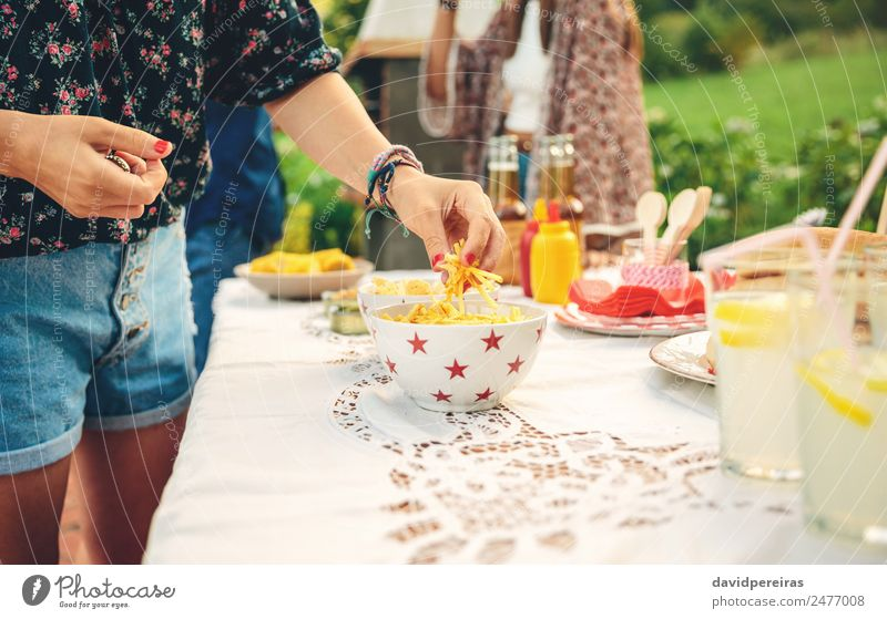 Frau Hand nimmt Pommes frites Kartoffeln aus der Schüssel Brot Limonade Alkohol Bier Teller Schalen & Schüsseln Lifestyle Freude Freizeit & Hobby Sommer Garten