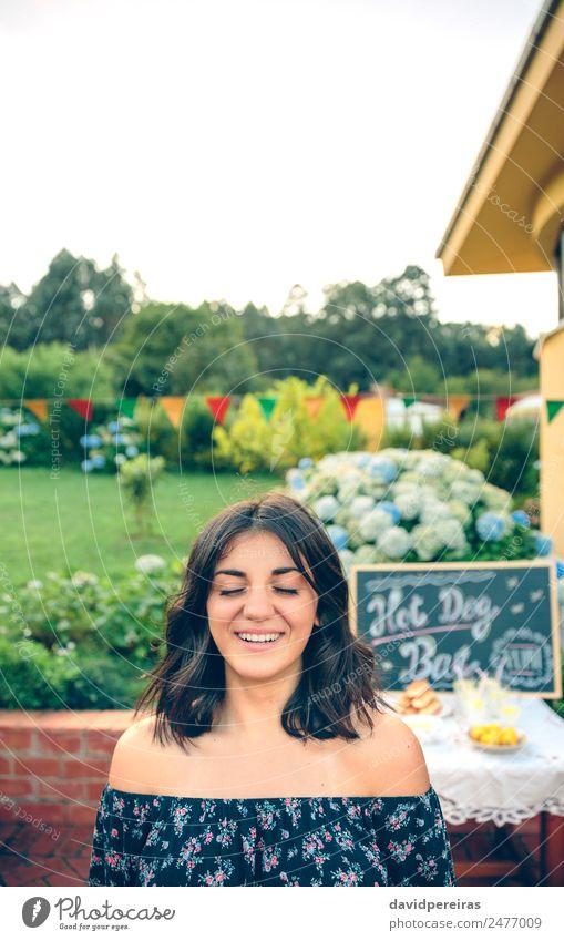Junge Frau mit geschlossenen Augen, die über den Naturhintergrund lacht. Mittagessen Limonade Lifestyle Freude Glück Freizeit & Hobby Sommer Garten Tisch Tafel